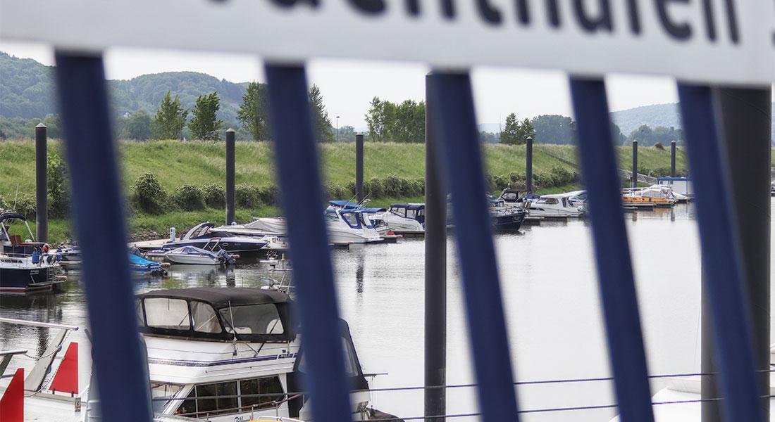 Blick durch blaues Gitter, die Streben in Unschärfe im Vordergrund, im Hintergrund das Hafenbecken mit dem Schwimmsteg der Molenseite