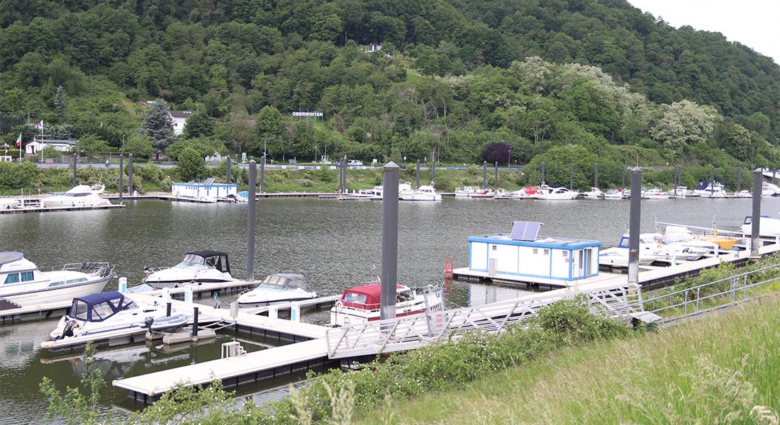 Blick ins Hafenbecken von der Mole aus, beide Steganlagen sowie die Sanitärcontainer im Fokus