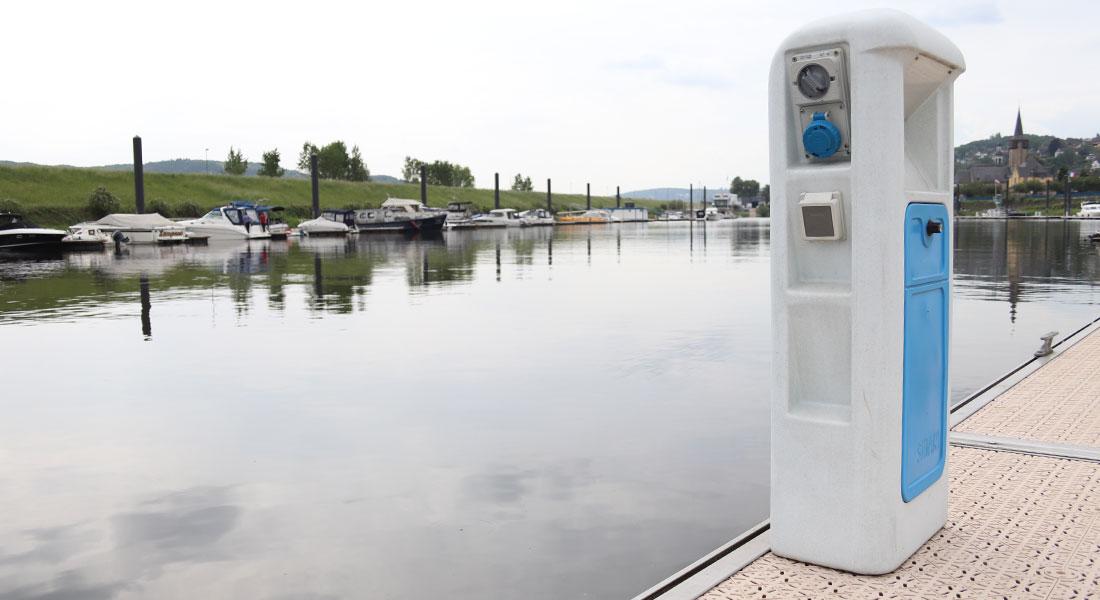 Stromsäule für Dauerlieger auf dem Schwimmsteg, das Hafenbecken und die Steganlage der Molenseite im Hintergrund