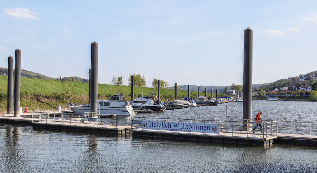 Hafeneinfahrt mit halbgeschlossener Schwimmbrücke, im Hintergrund Boote am Steg
