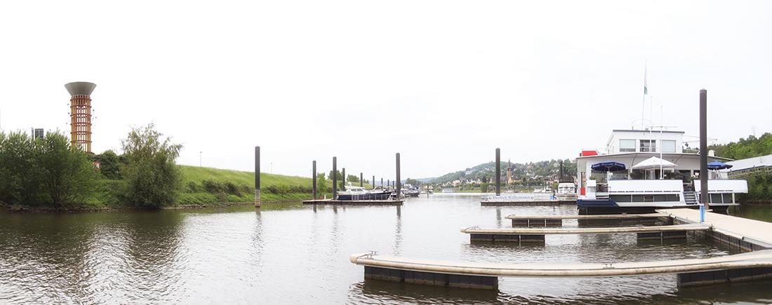Panoramaaufnahme von Hafeneinfahrt, links mit Skulptur Regenfänger auf der Spitze der Mohle, rechts das Pfannkuchenschiff, mittig die Hafeneinfahrt